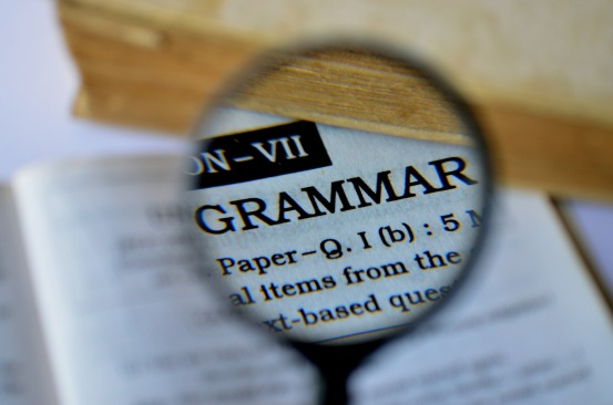 grammar nazi magnifying glass over book