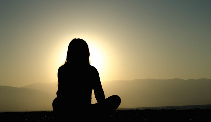 silhouette of woman facing sunset